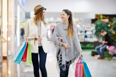 Two friendly girls with paperbags spending time in the mall Stock Photo