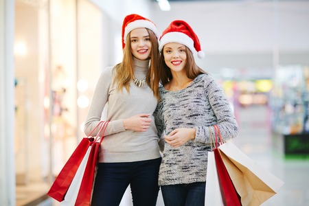 shoppingbag: Cheerful girls with handbags in shopping center Stock Photo