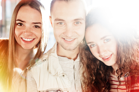 company person: Group of young friends looking a camera with smiles