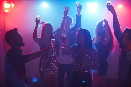 Amici con le mani alzate ballano con flauti di champagne Archivio Fotografico - 65996439