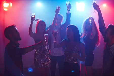 nightclub: Friends with raised hands dancing with flutes of champagne Stock Photo