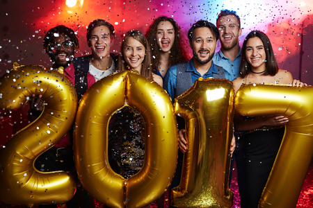 entertainment event: Group of joyful friends standing in confetti rain and holding 2017 shaped balloons