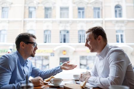 Jonge ondernemers praten tijdens de lunch pauze in cafe Stockfoto - 65996480