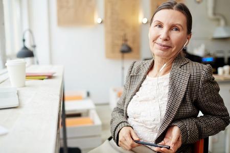 Femme d'affaires expérimentée avec des écouteurs travaillant dans un café