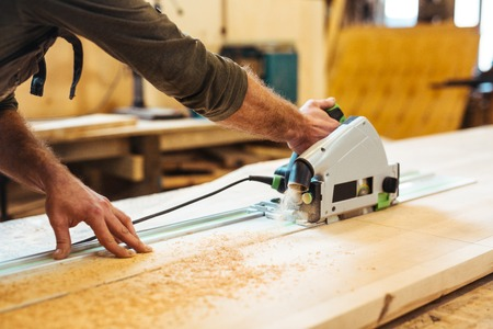 sawing: Man sawing wooden board in his workshop Stock Photo