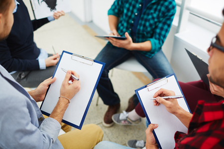 clipboard: Groupmates making notes at lecture on psychology Stock Photo