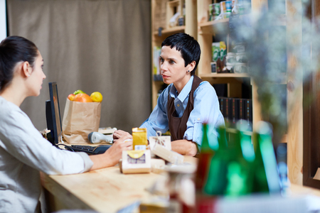 selfemployed: Self-employed assistant talking to young buyer in supermarket Stock Photo
