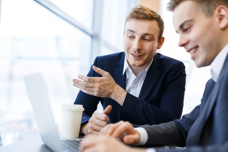 analyst: Analyst explaining data in laptop to colleague