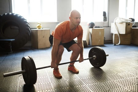 Strong man practicing difficult exercise with weight