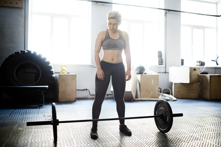 heavy weight: Fit young woman standing in front of heavy weight in gym Stock Photo