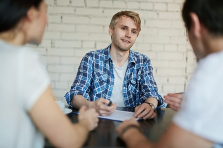 applicant: Young specialist being asked questions at appointment in modern company Stock Photo