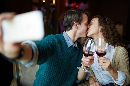 parejas enamoradas: Hombre joven que besa a su esposa y haciendo autofoto en el restaurante