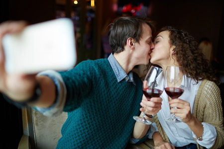 loving couples: Young man kissing his wife and making selfie in restaurant