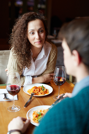 amorous: Amorous young woman looking at her boyfriend druing talk in restaurant Stock Photo