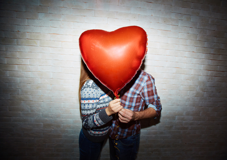 amorous: Red heart-shaped balloon and amorous couple hiding behind