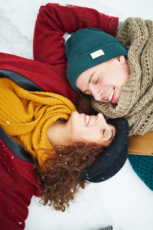 Happy couple in snowdrift looking at one another with smiles Stock Photo
