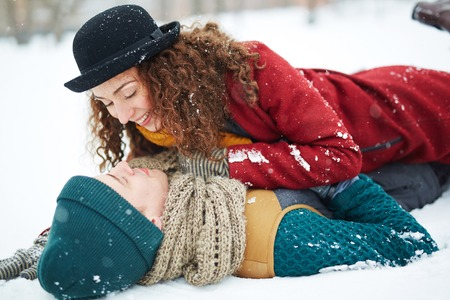 Happy young man and woman in winterwear lying in snowdrift Stock Photo