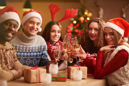 holiday tradition: Cheerful friends celebrating Christmas together Stock Photo