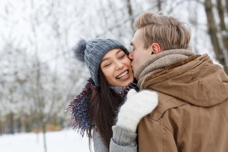 Guy kissing his girlfriend on cheek in embrace
