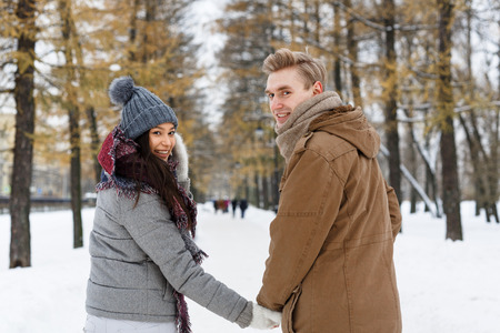 amorous: Amorous couple holding by hands during walk on winter day