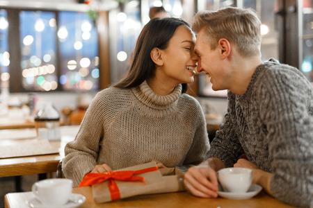 chica agradecido y su novio sentado frente a frente en el café el día de San Valentín Foto de archivo