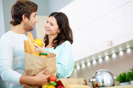 Amorous female with orange looking at her husband with packet of food Stock Photo