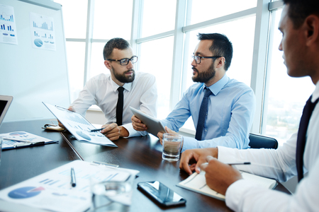 economists: Economists or analysts discussing financial data Stock Photo