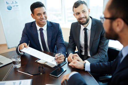 Happy businessman pointing at contract and looking at new business partner photo