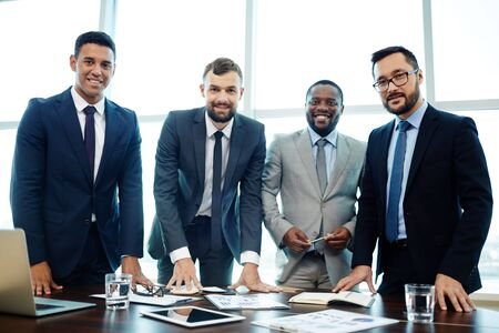 economists: Group of intercultural managers looking at camera Stock Photo
