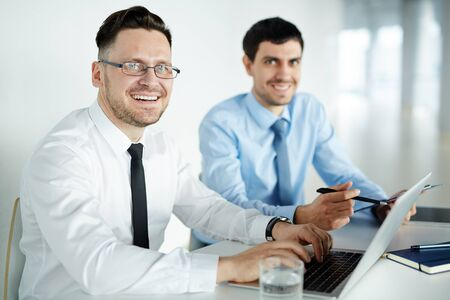 economists: Handsome businessman typing and looking at camera