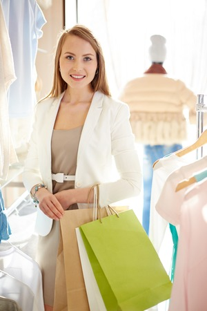 shopaholism: Young shopper with paperbagns visiting boutique Stock Photo