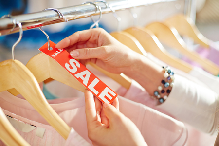 shopaholism: Girl choosing fashionable clothes during sale
