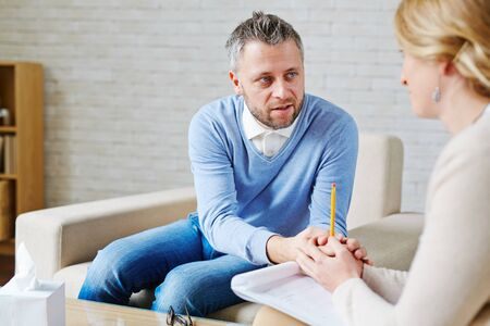 Man expressing empathy to young woman during psychological session