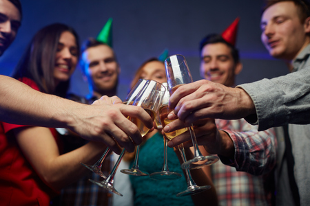 Young people clinking flutes with champagne at birthday party Stock Photo