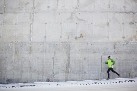 gente corriendo: Deportista que se ejecutan a lo largo de la pared de hormigón joven en invierno