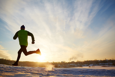 Back view of energetic sportsman running in winter Stock Photo
