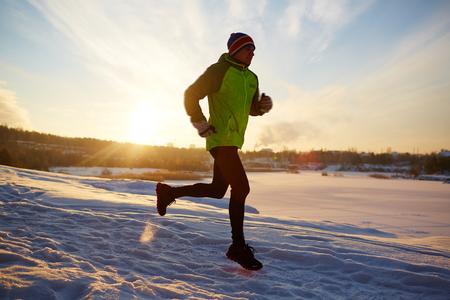Sportsman running in snowdrift at sundown