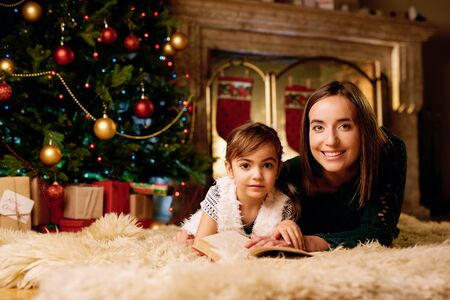 adorable child: Adorable child with mother reading book on xmas evening