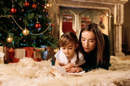 Mother and daughter reading xmas fairy-tales photo