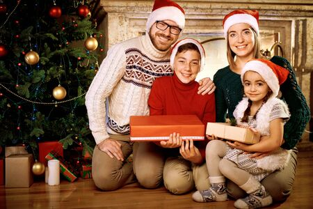 Cheerful family with gifts looking at camera photo
