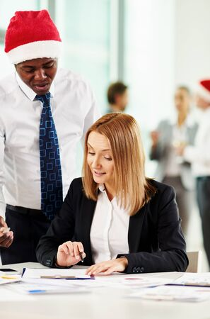economists: Co-workers discussing business document on xmas eve Stock Photo