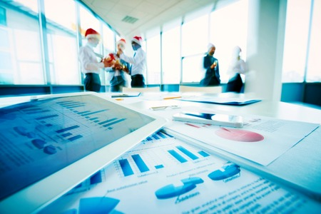 economists: Financial papers on workplace and group of business people celebrating xmas on background