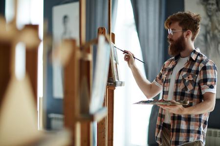 competencias laborales: hombre hábil con la brocha que incorpora sus ideas en papel Foto de archivo