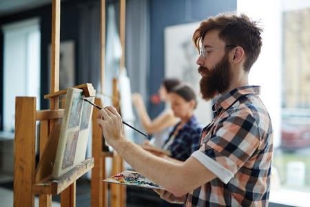 hombre pintando: Vista lateral de la pintura del hombre con barba en el arte del estudio Foto de archivo