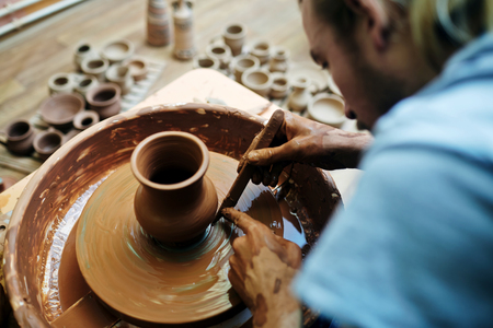 selfemployed: Self-employed potter using special tool while making clay item