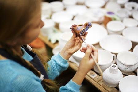 pottery: Girl painting clay bird in workshop