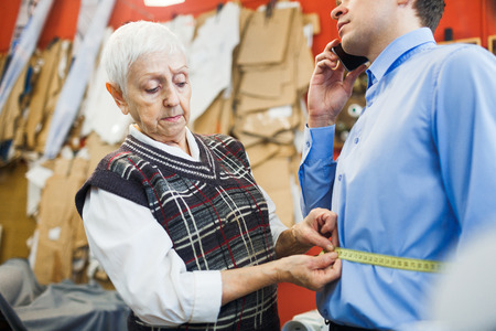 girth: Female tailor measuring waist of young businessman in blue shirt