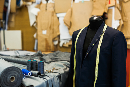 Unfinished jacket on dummy and sewing accessories in tailoring shop Stockfoto