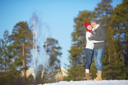 Affectionate couple embracing in the forest on wintery day Stock Photo