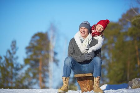 Attractive guy and girl in winterwear spending leisure in the forest photo
